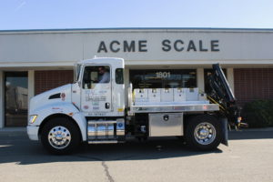 semi truck with scales in the back parked in front of acme scale company